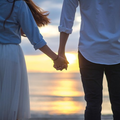 Couple holding hands beach scene